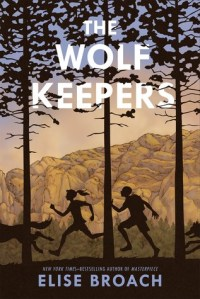 The wolf keepers boy and girl silhouette running between tall tress behind wolf