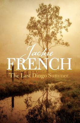 Jackie French The last dingo summer small lake surrounded by marsh and fields lone tree behind words wooden fence along edge of water light brown yellow sky
