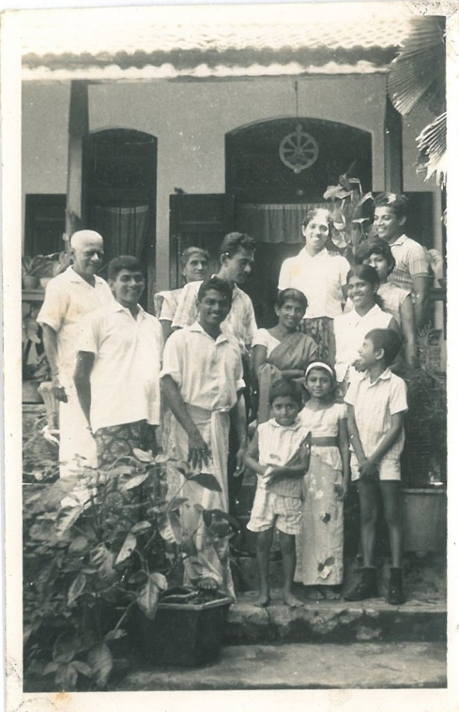 family photo black and white in front of house small kids in front and men and women behind all smiling