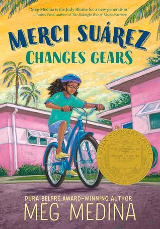 Merci Suarez changes gears blue and green letters across yellow sky palm trees in corners pink buildins young girl with brown hair and blue top and shorts riding blue bicycle on street