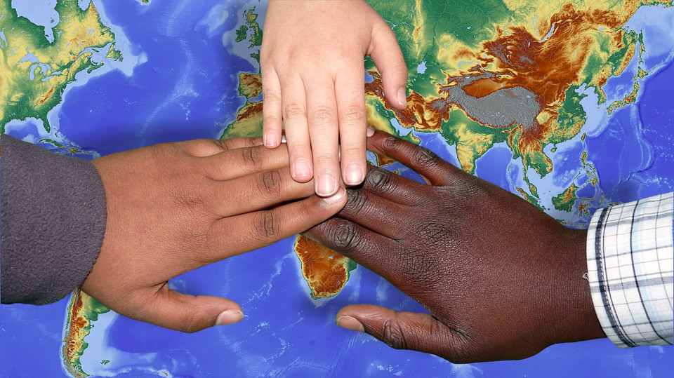 hands touching three colours white, brown, and black underneath map of world