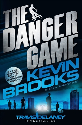 The Danger Game white letters. Kevin Brooks in blue letters. boy on bike beside The. boy and men behind him. blue sky and buildings behind him.