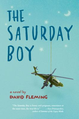 The Saturday Boy in dark blue letters across light blue background. stars and crescent moon in white above letters. army helicopter hanging from D in Saturday.