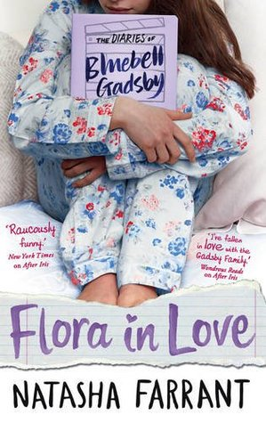 young girl in blue and red flowery pyjamas holding book under arms sitting on bed. text at bottom Flora in love in purple. Natasha Farrant in black.