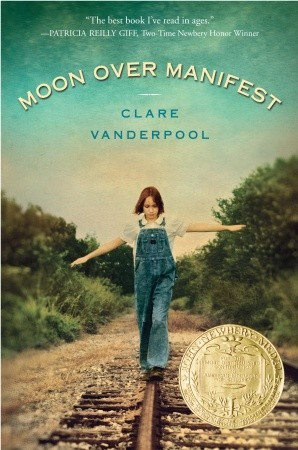 light blue-green sky with girl walking on rail tracks with arms outstretched wearing denim dungarees. bushes beside tracks. Moon over Manifest in arch over top in white letters and Clare Vanderpool in blue letters underneath. yellow seal of Newbery medal in bottom right corner.
