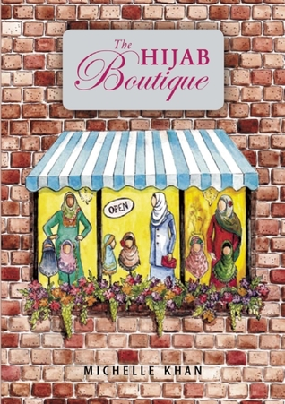 large background of brick wall. sign above shop window in middle. sign has pink lettering 'The Hijab Boutique.' window has three panels with images of ladies wearing different coloured hijabs. flowers along bottom of window and has blue panel above.