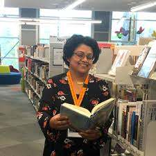 image of woman holding book inside library. lights above. woman in black and flowery dress with bright orange lanyard around neck.