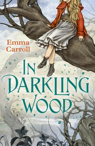 book cover image with white background of old looking trees. Emma Carroll in red letters and In Darkling Wood in blue letters. large tree branch protruding from right of image with image of girl in red coat and silver skirt sitting on branch with her head not visible. images of flowers at bottom edge and blue petals around blue letters.