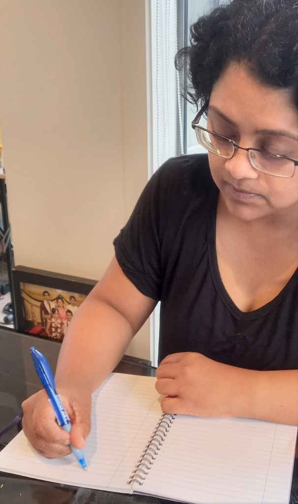 woman in black top with glasses writing on book with blue pen front profile