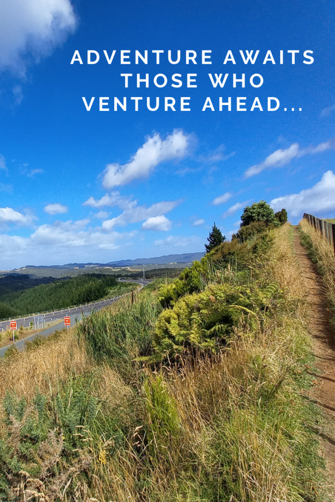image of green hills and road carving through. blue sky with small clouds. small path and fence on right edge of image. quote in sky in white letters reads Adventure awaits those who venture ahead...