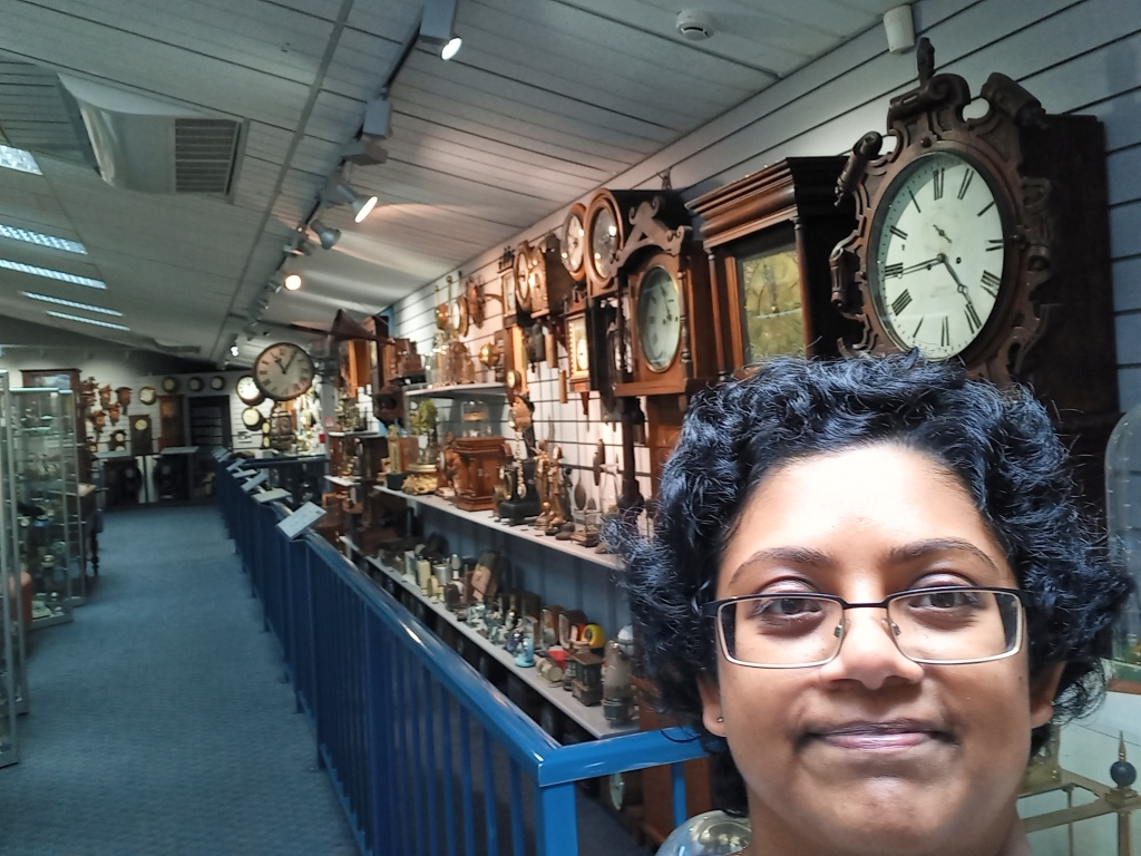 face of girl in glasses in right bottom. display of clocks of different sizes and shapes behind her in low-ceilinged building.