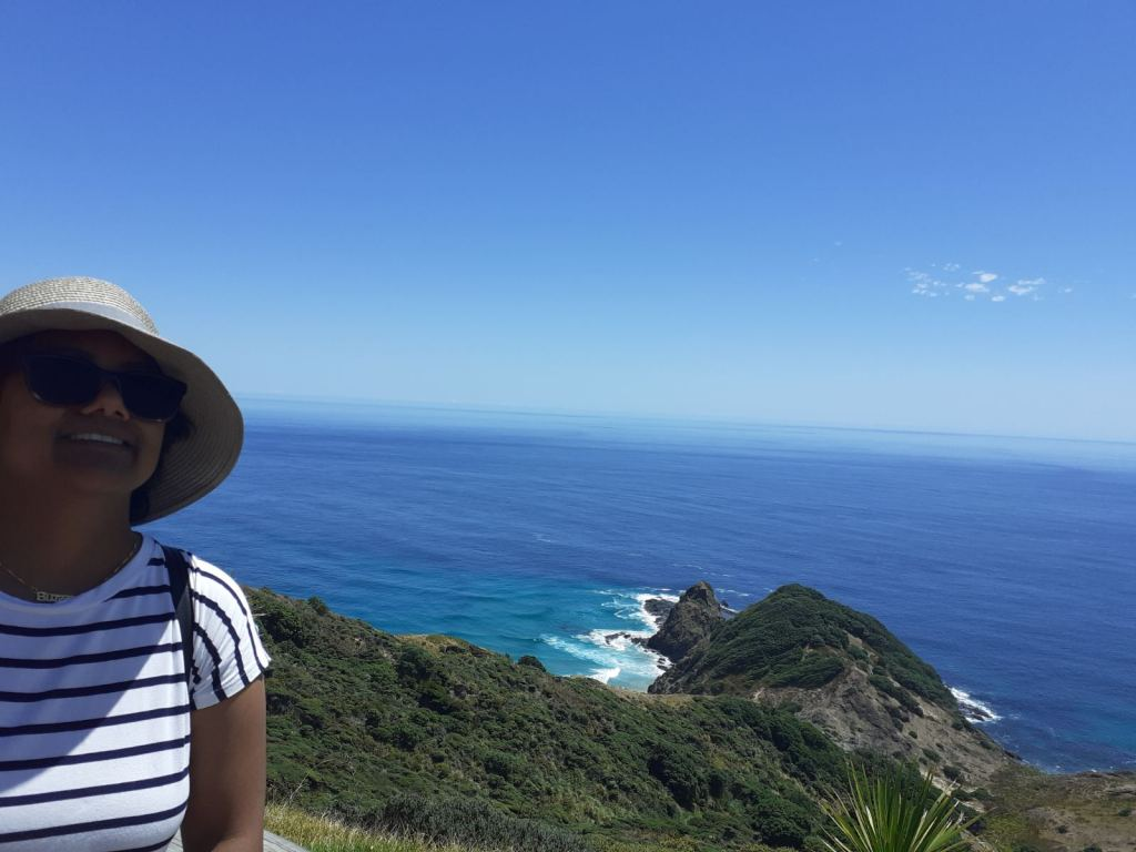 girl in striped shirt with sunglasses and hat in bottom left corner. blue sky and sea with point of land jutting out with while waves around. green trees and grass in between.