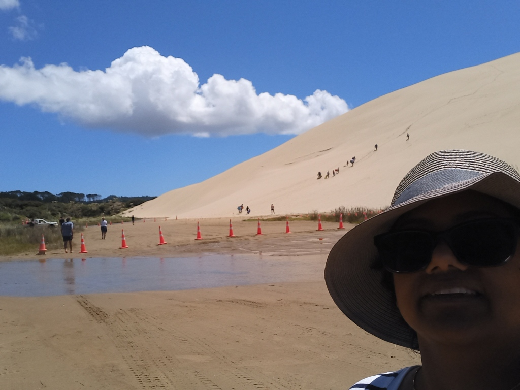 girl with sunglasses and hat in right bottom corner. behind large sand dune with people climbing and white cloud in middle of blue sky. small stream in between.