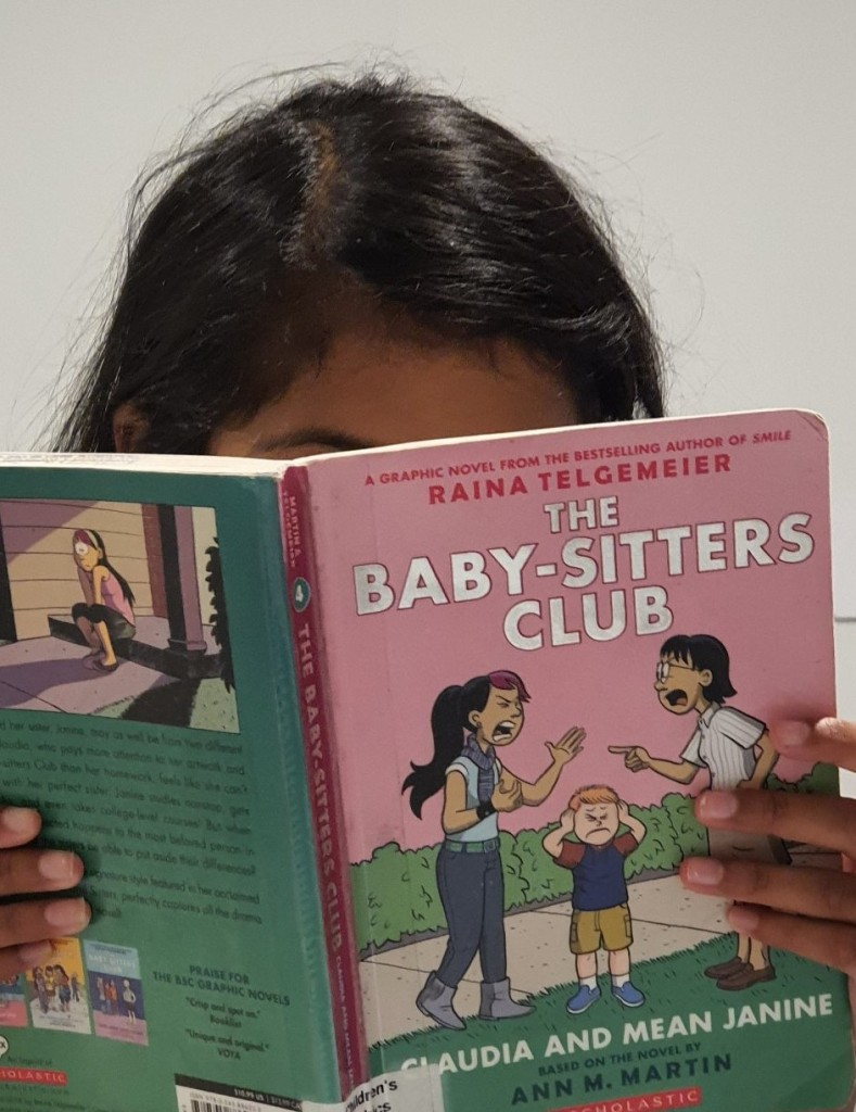 image of girl holding book. top of dark hair showing above pink and green The Baby-Sitter's Club book. pale grey background behind.