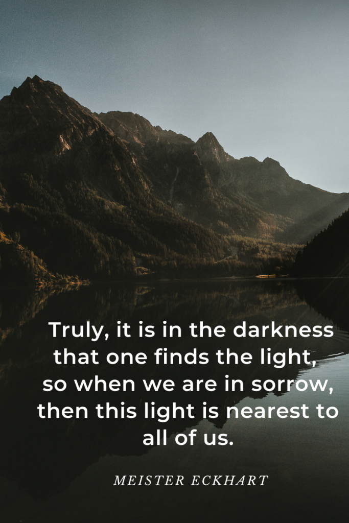 image of mountains and lake in darkened hues. patch of slightly darker sky on top. quote in white letters at bottom over lake. quote reads 'Truly, it is in the darkness that one finds the light, so when we are in sorrow, then this light is nearest to all of us.' Meister Eckhart.