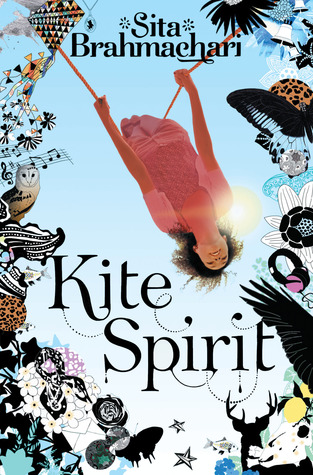 blue cover background of sky and sun shining from above shoulder of image of young girl taken from mid-flight on swing while upside down. around edges images of flowers, woodland creatures, bells, kites, musical notes. large black letters at middle bottom read Kite Spirit. smaller letters at top read Sita Brahmachari.