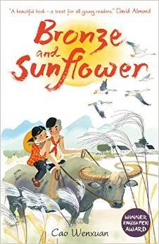 cover image of two small children riding on top of buffalo in fields. small buildings in middle ground. cranes flying in sky. orange yellow sun in middle. red letters over sun reads Bronze and Sunflower.
