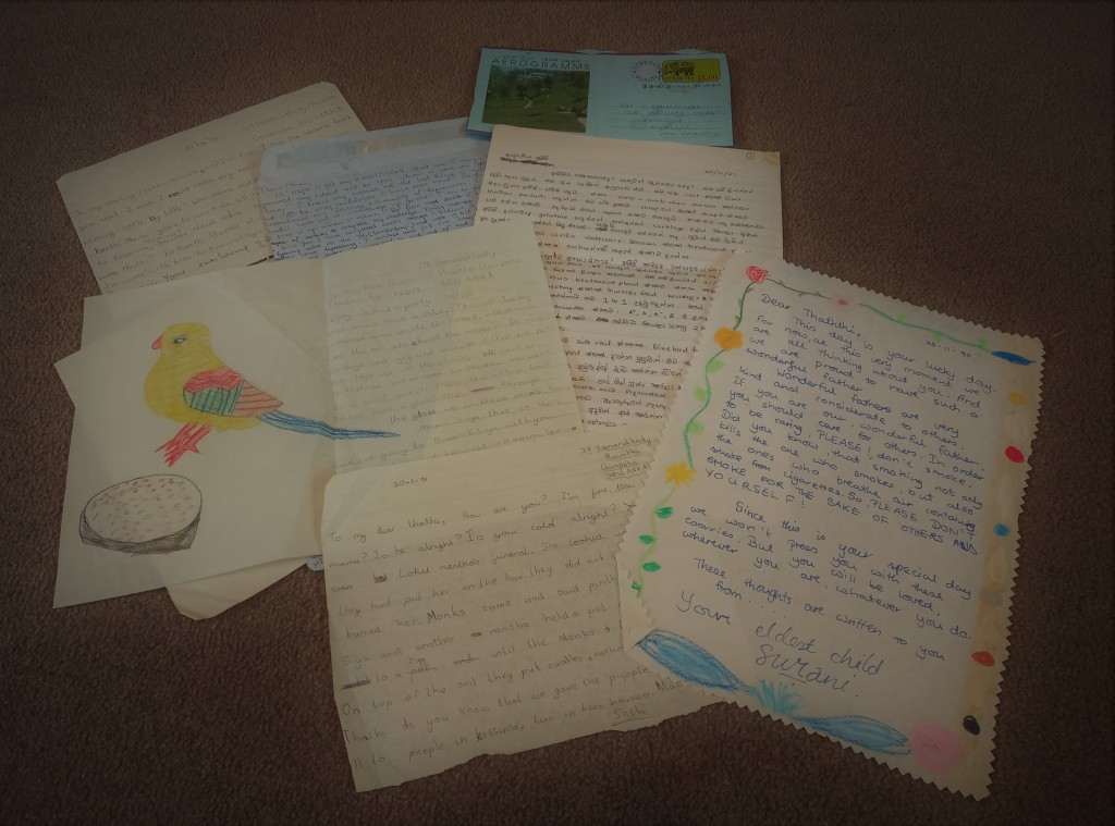 image of seven letters on brown background. blue coloured sheets at top. handwritten letters on white paper, some have handdrawn picture of bird and another has flowers along edge.
