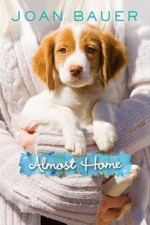 image of small white and brown dog held in arms of someone wearing white jumper. blue letters at top read Joan Bauer. white letters across blue in middle read Almost Home.